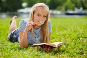 The beautiful young woman lies on a grass in park with the book and a dandelion.
